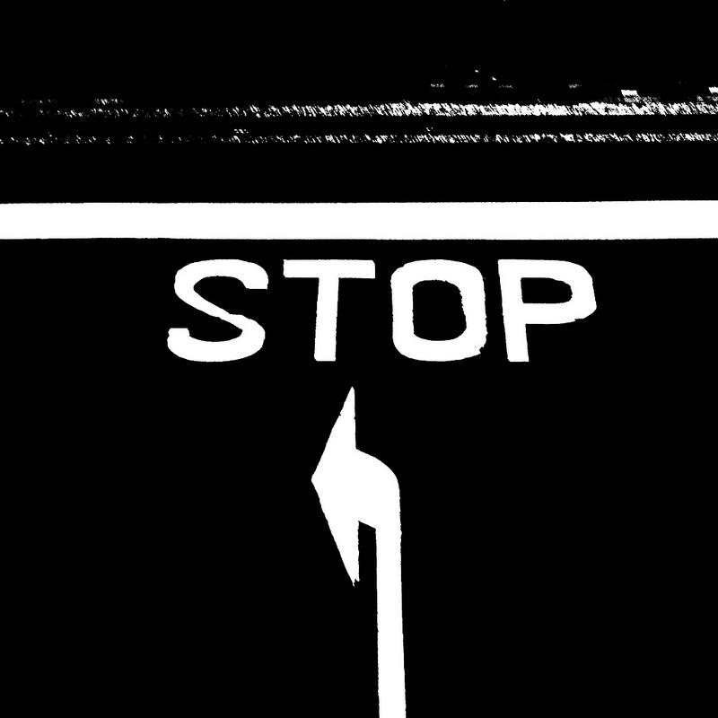 """Photo en blanc sur noir sur laquelle il est inscrit """"stop""""."""