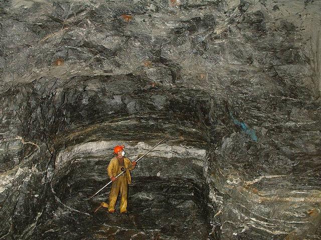 Mineur dans une mine d'or devant une veine de quartz et d'or.
