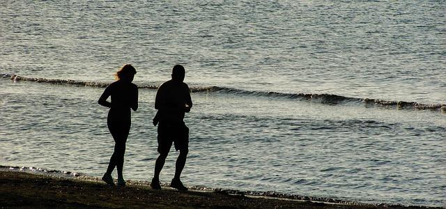 Un homme et une femme courent sur la plage.