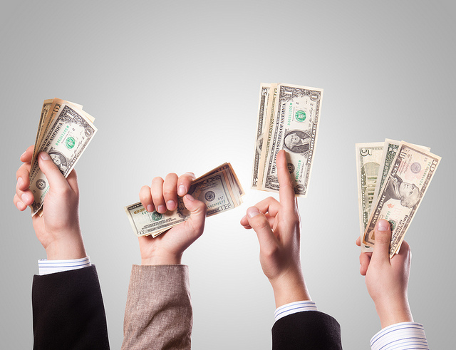 Bras d'hommes tenant des billets de banque.