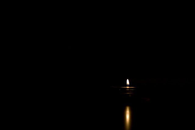 Une bougie brille seule dans le noir.