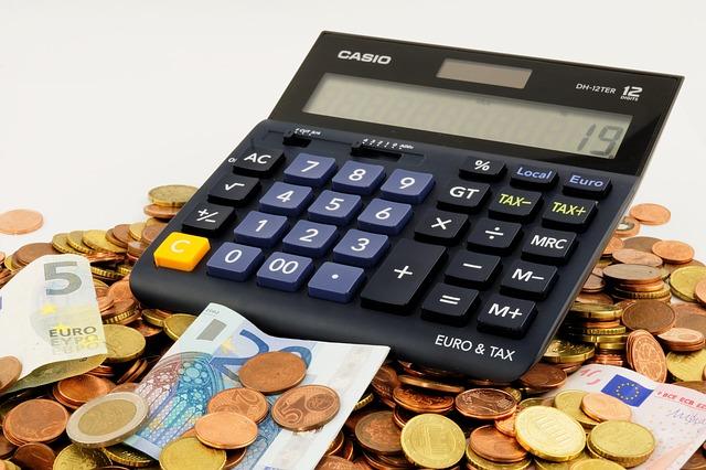 Photographie d'une calculatrice sur un tas d'argent.
