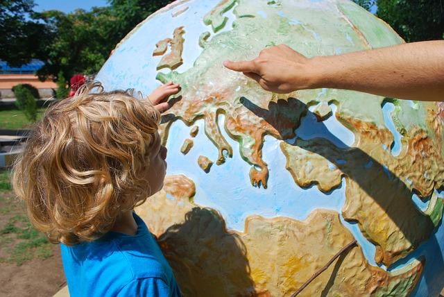 Enfant découvrant l'Europe sur un globe terrestre.