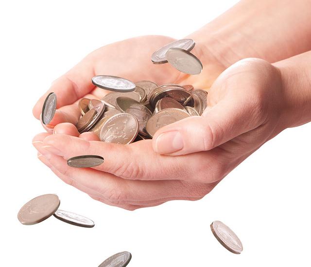 Mains remplies de pièces d'argent.