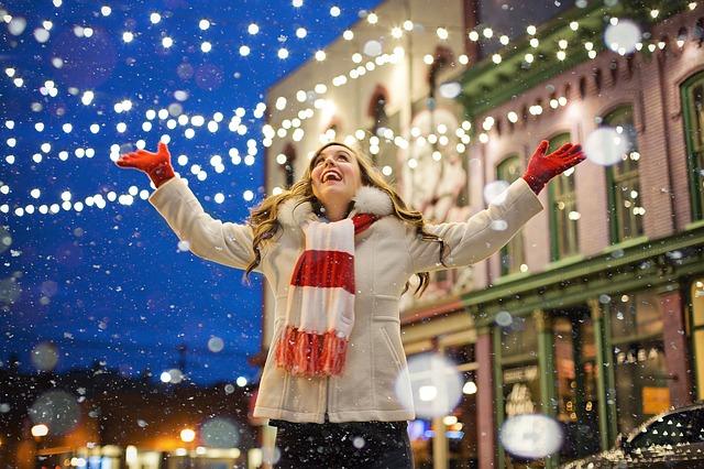 Femme souriant pendant que la neige tombe.