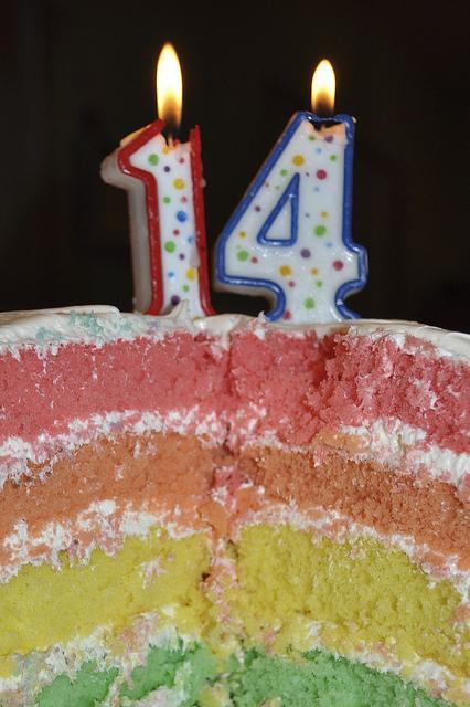 Un gâteau arc-en-ciel avec le chiffre 14 en bougies.