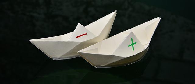 Deux bateaux en papier avec un plus et un moins dessinés au feutre.