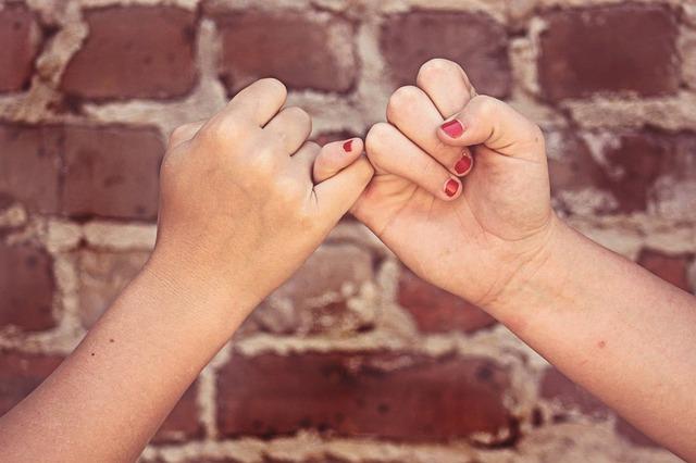 Deux mains avec les petits doigts entremêlées pour se tenir une promesse.
