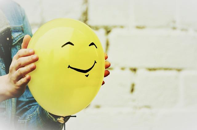Ballon jaune sur lequel est dessiné un smiley qui sourit.