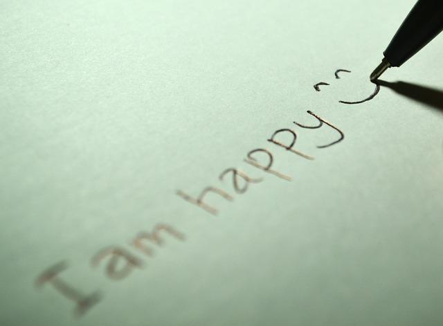 """Feuille sur laquelle il est écrit """"I am happy""""."""