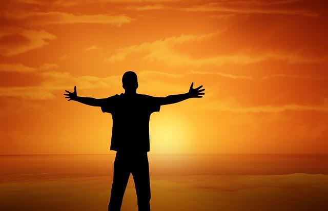 Homme qui tend les bras face au coucher de soleil.