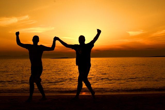 Des personnes joyeuses sur une plage les bras en l'air.