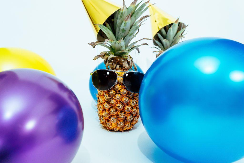 Photographie d'un ananas avec un chapeau et entouré de ballons pour célébrer les dix ans de SuperChance100.