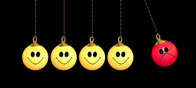 Quatre billes jaunes avec un visage souriant, contre une bille rouge au visage mécontent.