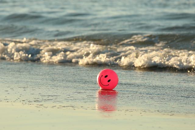 Dessin d'un smiley qui sourit sur une petite balle rose sur la plage.