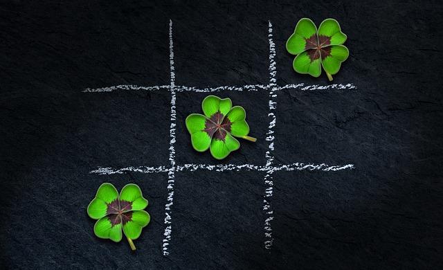 Trois trèfles à quatre feuilles alignés dans un jeu de morpion.