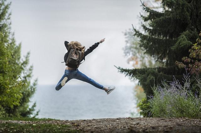 Jeune femme de dos sautant de joie après avoir gagné à l'Euro Millions.