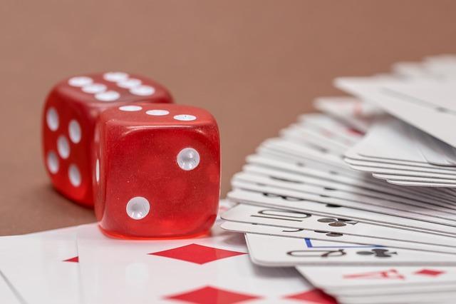 Jeu de cartes et deux dés posés sur une table.