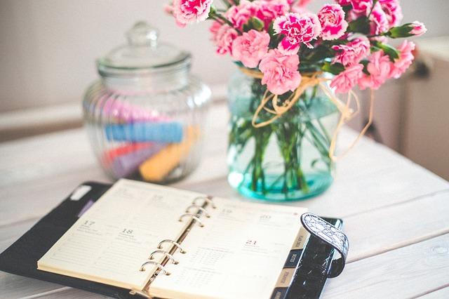 Agenda papier et pot de fleurs posés sur un bureau.