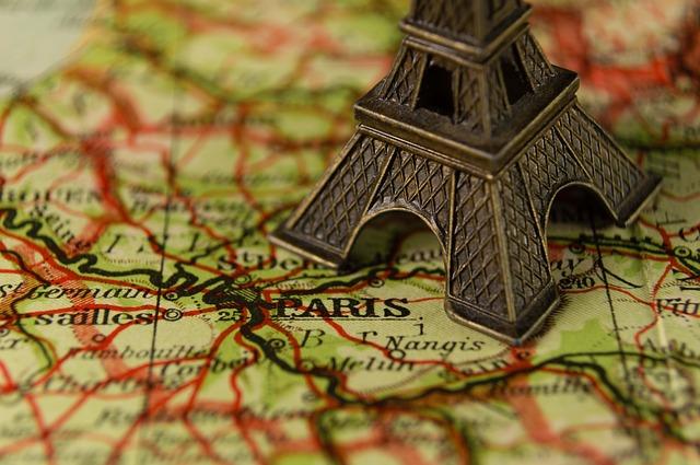 Carte de France sur laquelle est posée une petite tour Eiffel.