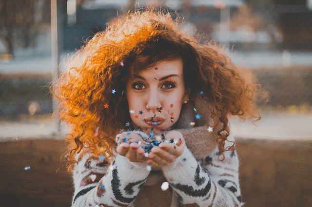 Jeune femme qui souffle sur des confettis d'étoiles.