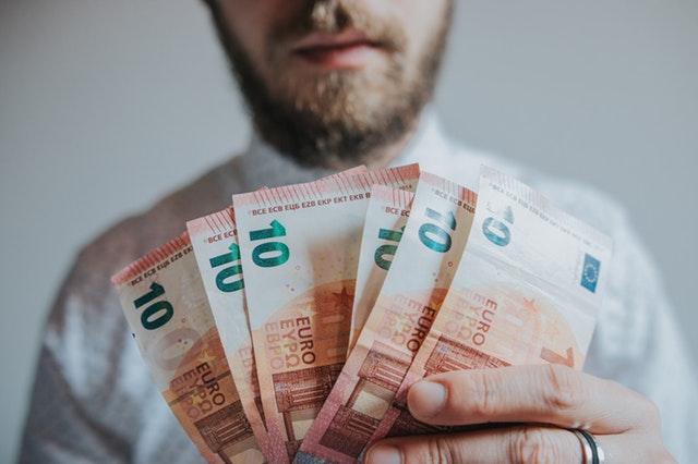 Homme qui tient des billets de dix euros dans sa main.