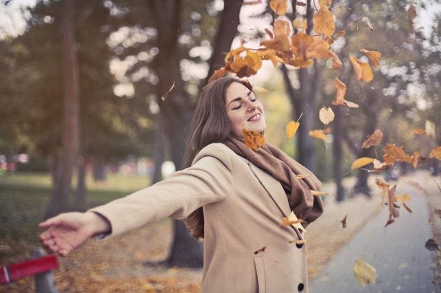 Jeune femme heureuse qui lance des feuilles.