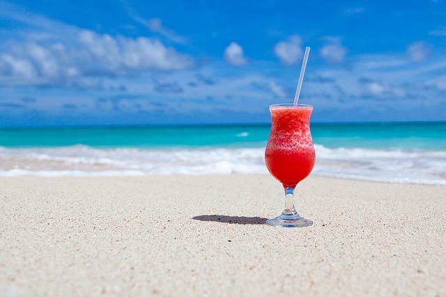 Verre de cocktail sur une plage de sable fin.