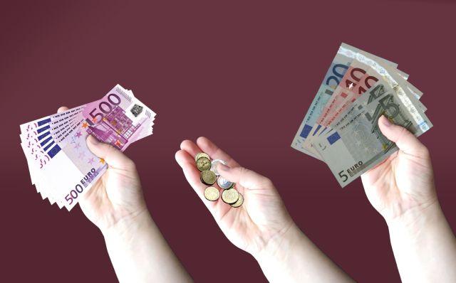 Des mains qui tiennent des billets de banque.