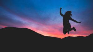 Personne qui saute de joie avec le coucher de soleil en fond.